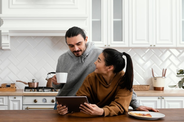 Couple taking breakfast in the kitchen and using a tablet