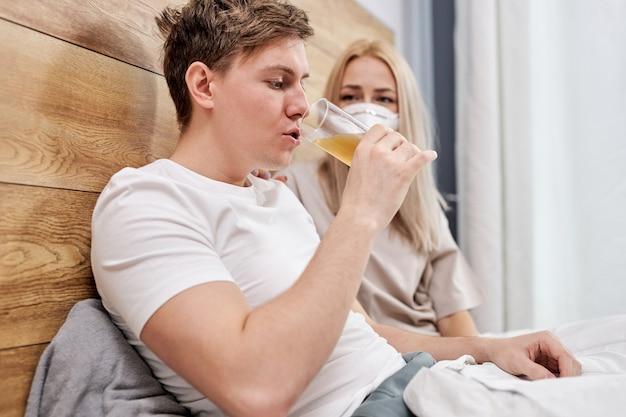 Пара, принимающая лекарства, таблетки витамины, сидя на кровати, страдает от covid-19, они вместе находятся дома на карантине. оставайся дома во время пандемии