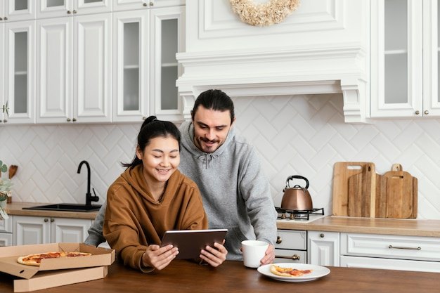 Couple taking morning meal in the kitchen and using a tablet