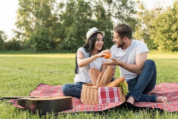 Couple taking an orange on a picnic blanket