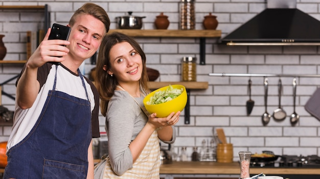 Couple taking photo with vegetable salad