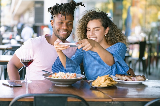 Couple taking photos to the food with a mobile phone.