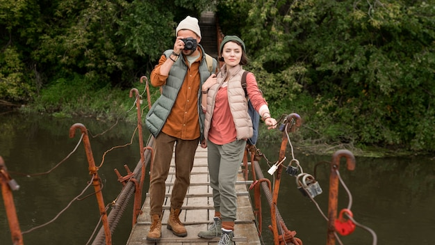 Couple taking photos on wooden bridge
