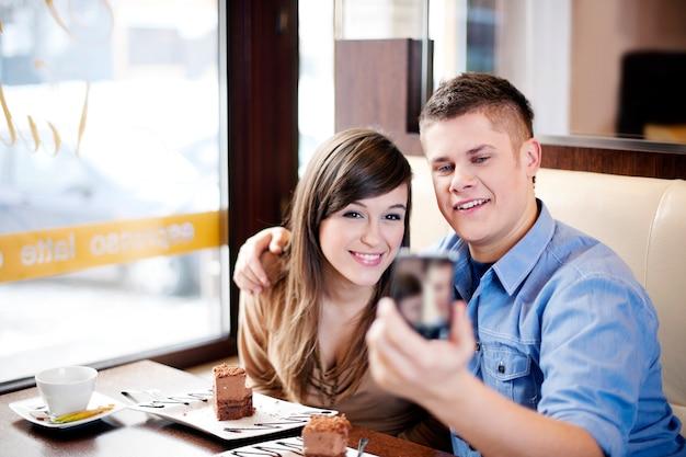 Пара фотографируется в кафе