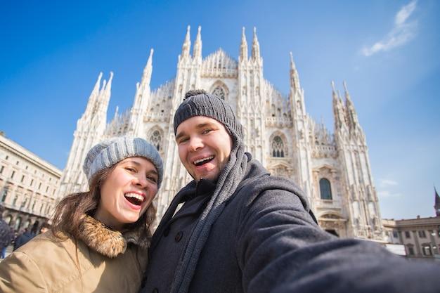 ミラノのドゥオーモ広場で自画像を撮るカップル