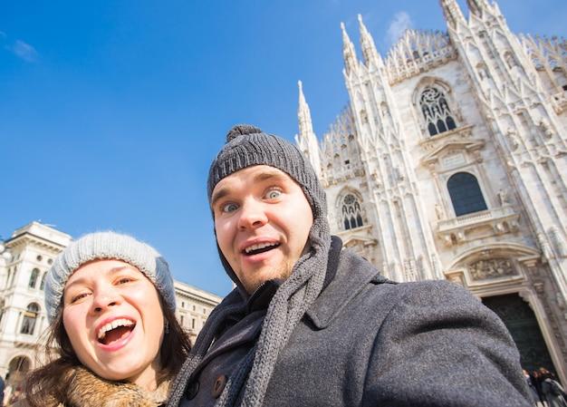 ミラノのドゥオーモ広場で自画像を撮るカップル。