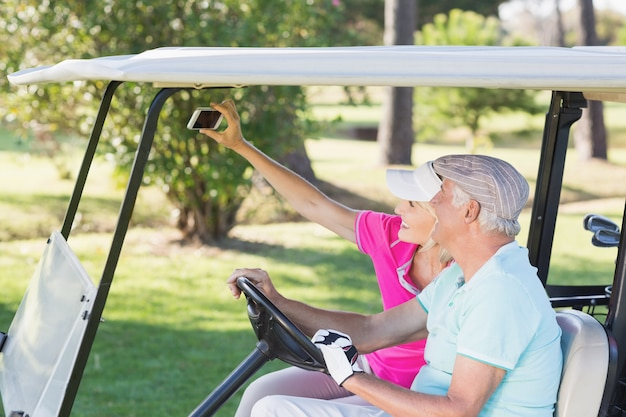 Couple taking self portrait while sitting in golf buggy