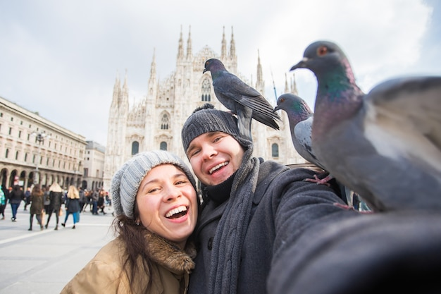 ミラノのドゥオーモ広場で鳩と自画像を撮るカップル。