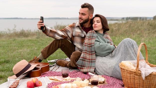 ピクニックで自分撮りをしているカップル