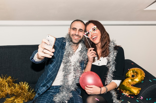 Couple taking selfie on couch