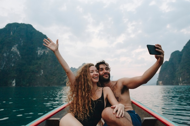 Couple taking selfie on a longtail boat