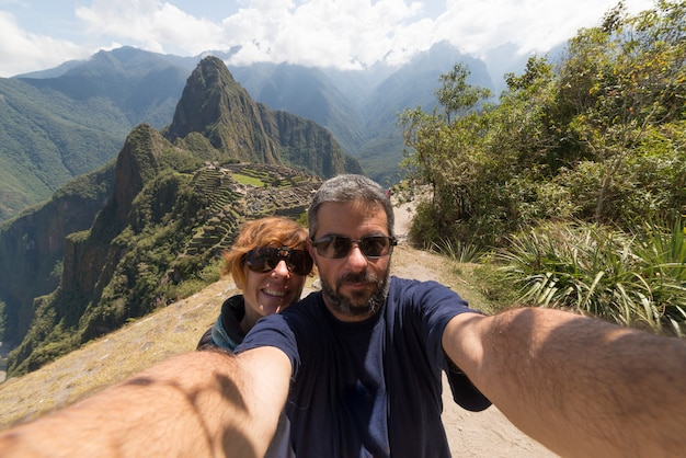 Couple taking selfie at machu picchu, peru