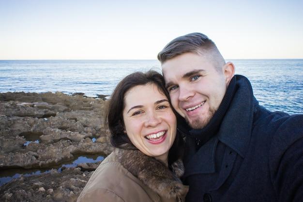 海の近くで自分撮り写真を撮るカップル