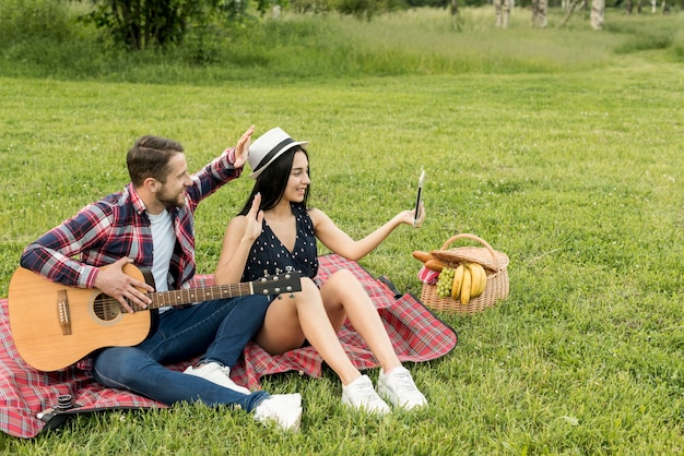 Couple taking a selfie on a picnic blanket