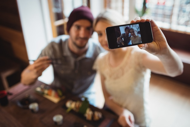 Couple taking selfie while having sushi