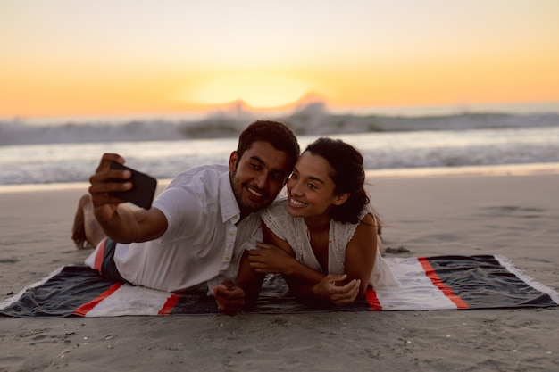 Couple taking selfie with mobile phone on the beach