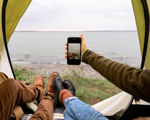 Пара, делающая селфи со смартфоном в палатке