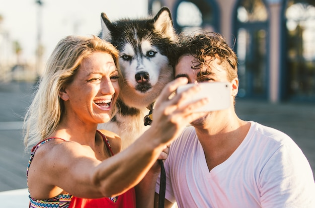 Couple taking selfie with their husky