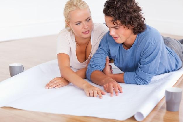 Пара говорит о своей будущей комнате с планом