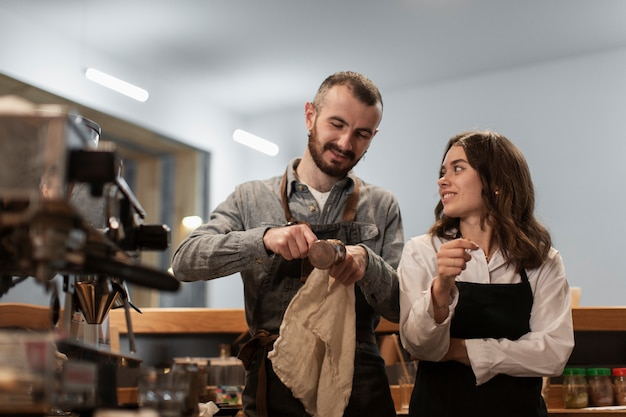 Couple talking and cleaning coffee equipment