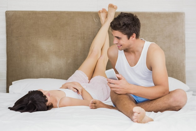 Couple talking to each other while relaxing on bed in bedroom