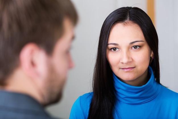 カップルが話している。後ろの画像からの女性と男性の顔