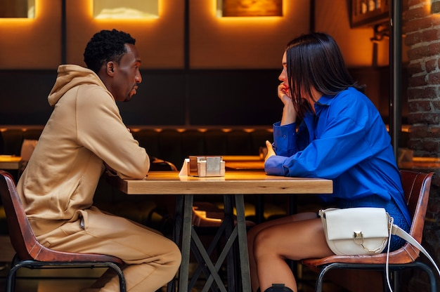 コーヒーショップの側面図で話しているカップル