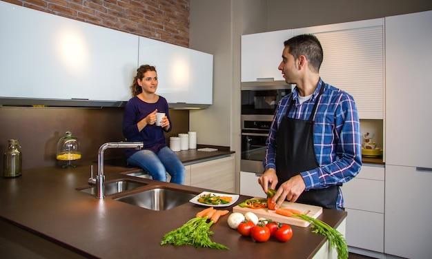 Пара разговаривает на кухне, пока муж режет овощи, чтобы приготовить еду