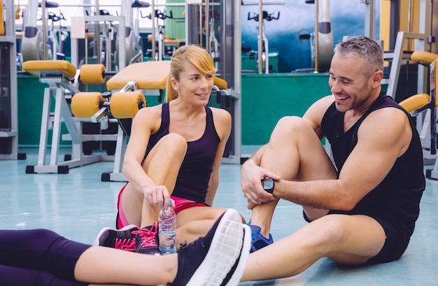 Couple talking and laughing sitting on the floor of a fitness center after hard training day