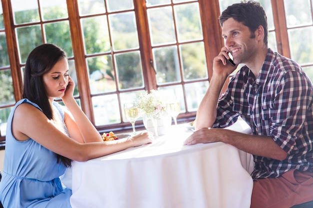 Couple talking on mobile phone in restaurant
