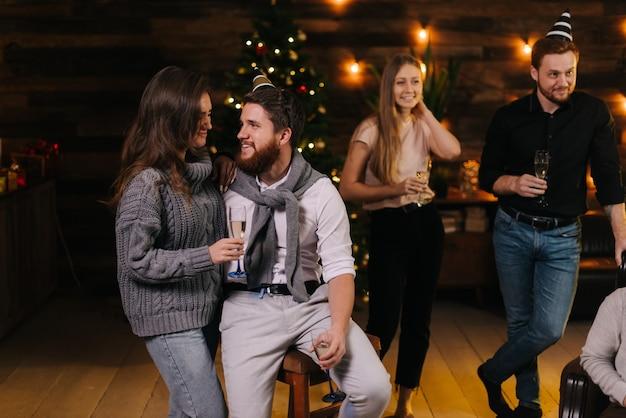 お祝いのクリスマスツリーを背景に大晦日に話しているカップル。恋人のボーイフレンドとガールフレンドは、お祝いに飾られた部屋でうまくコミュニケーションします。女の子は手にシャンパングラスを持っています。