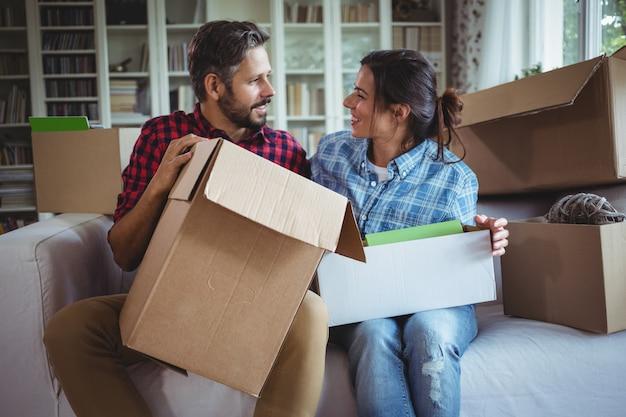 カートンボックスを開梱しながらソファで話しているカップル