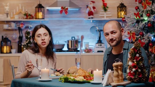 お祝いの夕食を楽しんでいるビデオ通話会議で話しているカップル