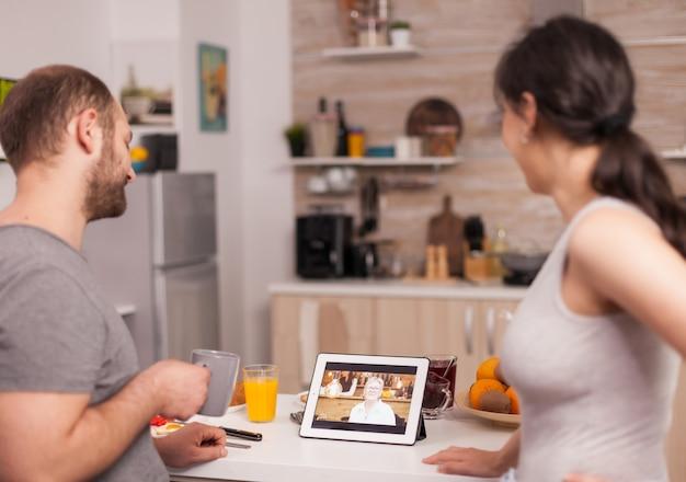 朝食時にビデオ通話で家族とオンラインで話しているカップル。午前中のビデオ会議、オンラインwebインターネット技術の使用、親戚との会話とコミュニケーション