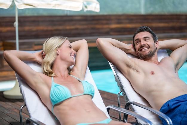 サンラウンジャーでリラックスしながら話しているカップル