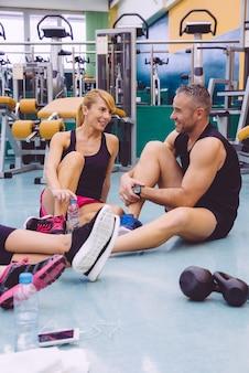 힘든 훈련을 마친 후 피트니스 센터 바닥에 앉아 친구들과 이야기하는 커플
