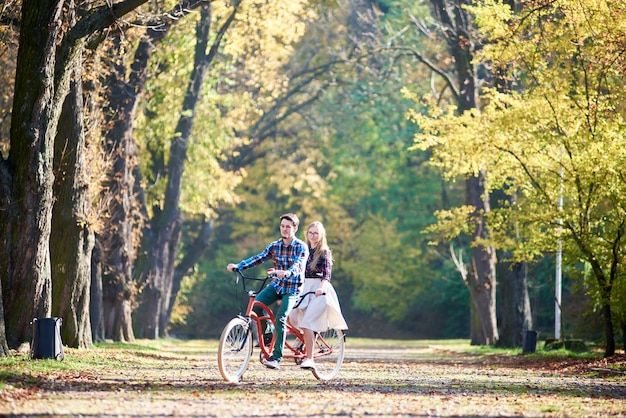 Couple on tandem bike in park