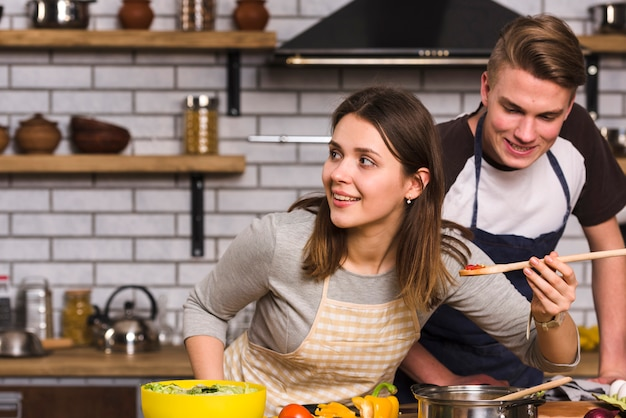 Couple tasting cooked meal