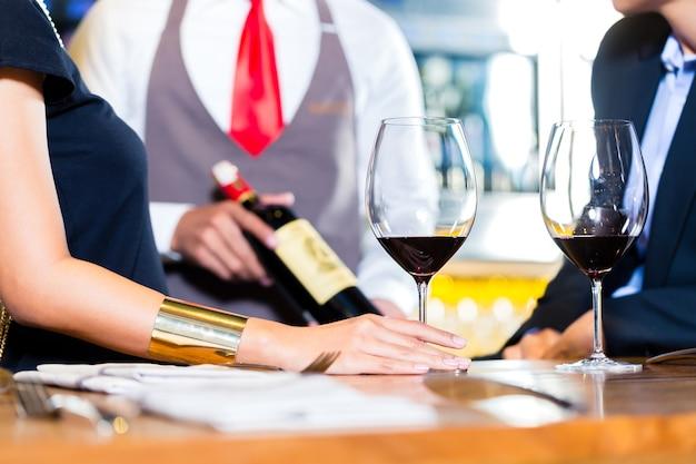 ワインショップで赤ワインを試飲するカップル