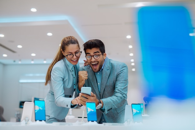 Couple at tech store looking for a new mobile phone.