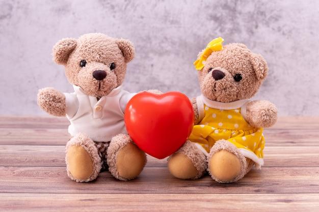 木製のテーブルの上の心とカップルのテディベア。バレンタインデーのお祝い