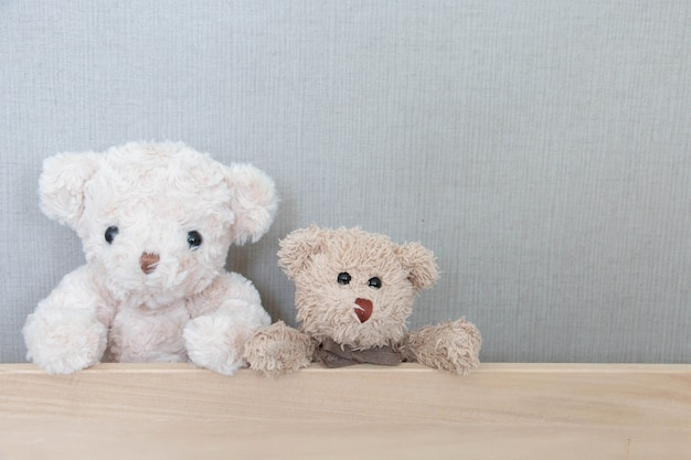 A couple of teddy bears are on wood board on grey