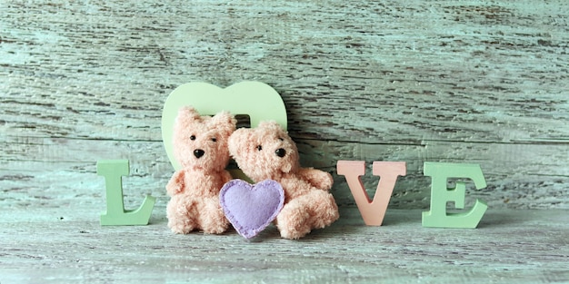 Couple of teddy bears toys and the word love from wooden letters, heart