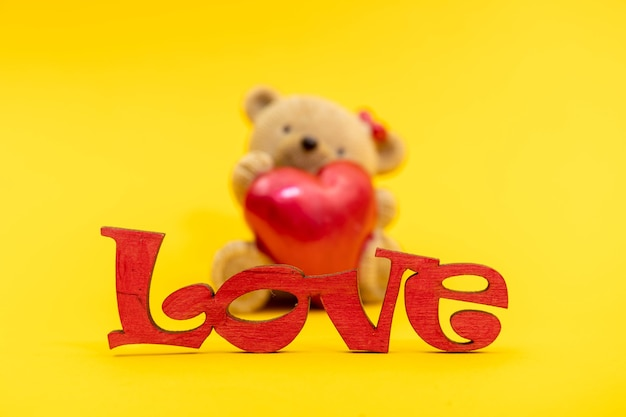Couple of teddy bears toys and the word love from wooden letters, red hearts. valentine day concept. postcard template.