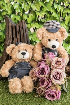 Couple teddy bears with roses in the garden
