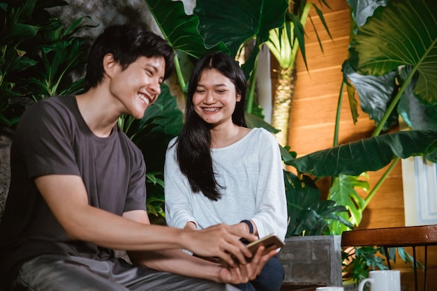 Couple of teenagers laughing use smartphone together while sitting on a wooden bench in the garden of the house