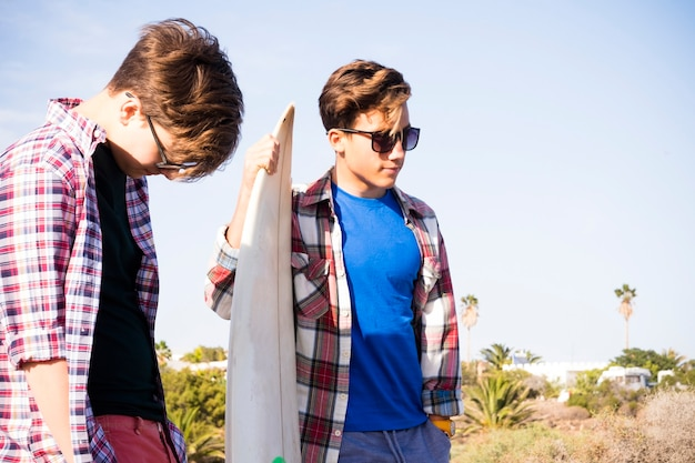 Couple of teenagers with friendship at the beach looking at the sea with a surftable talking between - happy day together ready to go to surf
