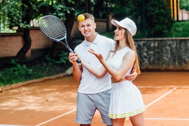 カップルテニスプレーヤー。陽気な笑顔を与え、ラケットを持って、ユニフォームを着ている運動の女性と男性。