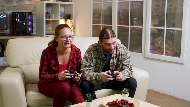 Couple in their 30's relaxing playing video games using wireless controllers. happy relationship.