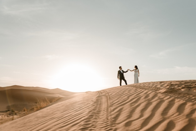 A couple in their wedding clothes on top of a desert dune at dawn